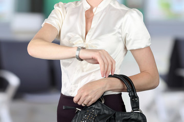 well- dressed businesswoman checking time on her watch