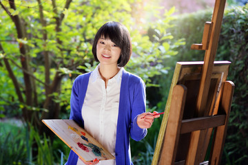 Happy woman painting a canvas in the garden