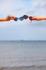 Hands with red and blue sunglasses shaped heart