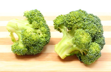 Portion of fresh green broccoli on wooden cutting board