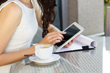 Girl spending time in a cafe using digital tablet