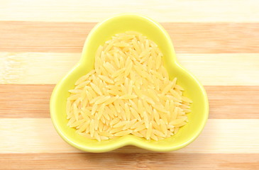 Yellow pasta in glass bowl on wooden cutting board