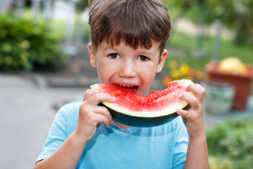 Little cute caucasian boy eat melon