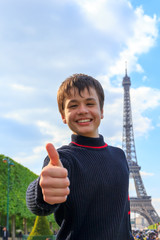 Cheerful teenager shows thumb up near Eiffel Tower (La Tour Eiff