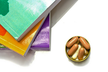 book and  capsule pills on white background