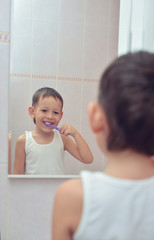 Boy brushing his teeth in front of mirror