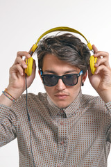 Retrato de un hombre escuchando música audífonos amarillos.