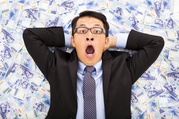 excited  business man lying on the new taiwan dollar