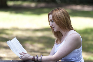 Pretty red haired girl reading in the park