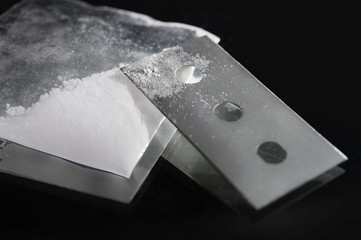 cocaine bag and drug stained razor blade in addiction concept