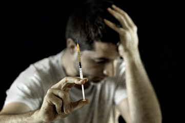 drug addict man and heroin or cocaine syringe addiction concept