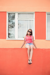 teenager girl sitting on background orange wall