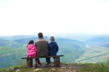Family on a mountain lookout observing nature