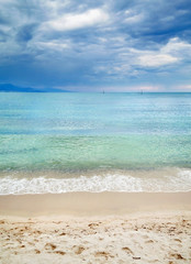 Sandy beach with clean blue waves and cloudy sky.