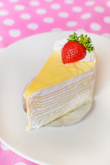 Crape cake with strawberry topping on pink dot