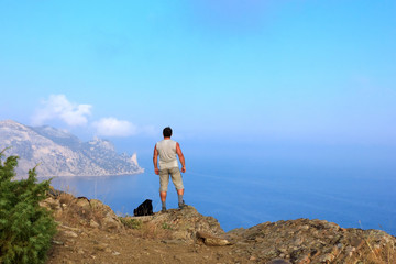 Traveler looks at the beautiful seascape from the mountain top