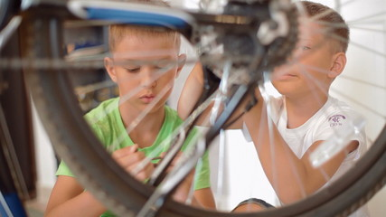 two little boys repairing a bicycle
