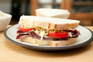 sliced roast beef sandwich with cheese and tomato and cole slaw