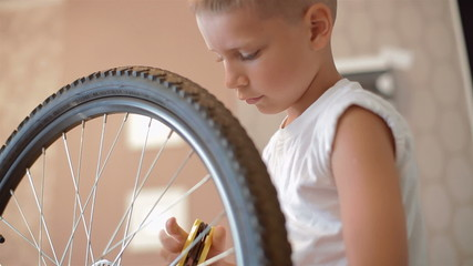 Little boy repairing a bicycle, he tightens the nuts and bolts