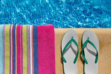 Pair of flip flop thongs and towel on the side of swimming pool