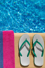 Pair of flip flop thongs and a towel at the swimming pool