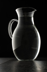 Glass water jug isolated on the black background