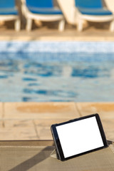 Blank digital tablet on a chair next to swimming pool