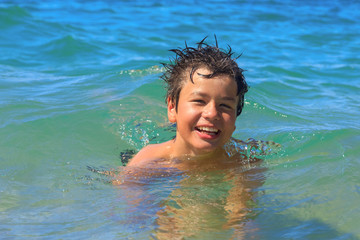 Happy young swims in the sea
