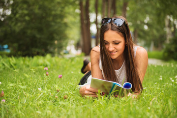 A young brunette woman lying on the grass outdoors with a magazi