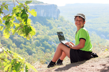 Smiling boy in green t-shirt with a netbook on top of the mounta