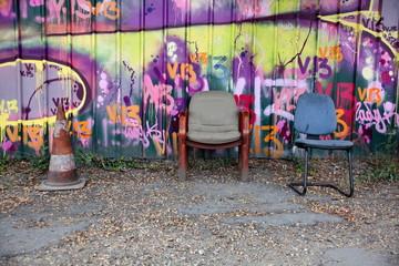 Fauteuils devant palissade de chantier avec graffitis