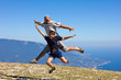 happy man and boy jumping on a background of mountains and sky a