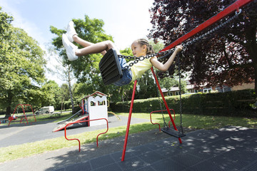 Young girl swinging high on a swing in a playground