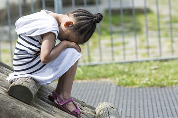 Young girl sitting with her head in her lap feeling sad
