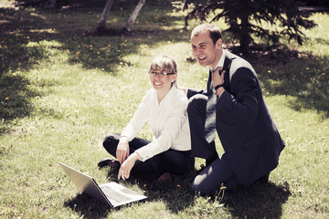 Young business people using laptop on nature