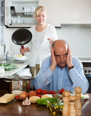 Mature couple having quarrel at kitchen