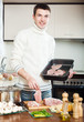 young  man cooking french-style meat at  home kitchen