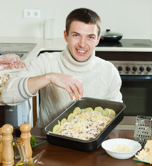 Man adding grated cheese in roasting pan