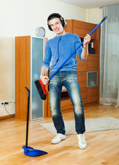 Happy man playing and dancing with broom at home