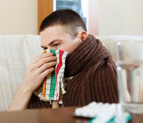 Ilness man in scarf using handkerchief