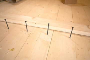 Installation of the floor in a house. Screws before tightening