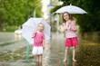 Two cute little sisters having fun under a rain
