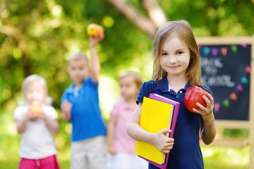 Excited little schoolgirl going back to school