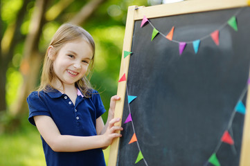 Very excited little schoolgirl by a chalkboard