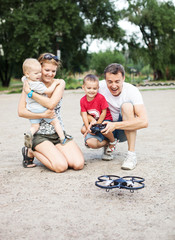 Family with two boys playing with RC quadrocopter toy
