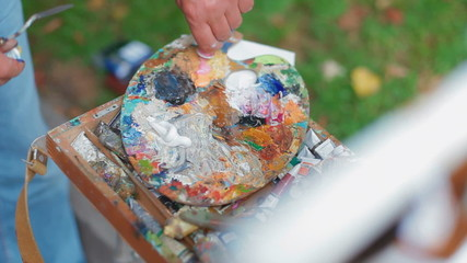 Artist squeezes the tube with oil paints on a palette