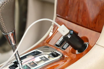 USB charger plug with charging cable on a car