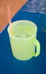 Green glass with ice Bright blue background