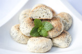 Handmade poppy seed cookies with a placed mint leaf on the side in a white bowl on a white background.