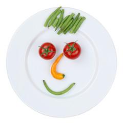 Gesicht aus Gemüse auf Teller freigestellt